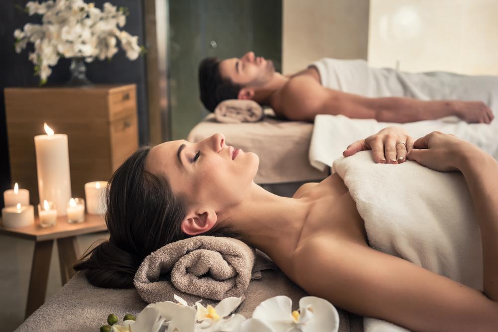 Junge Männer und Frauen, die sich auf Massagebetten im asiatischen Luxus-Spa und Wellnesscenter aufhalten